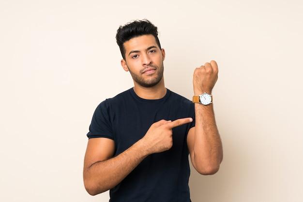 Junger gutaussehender mann über der lokalisierten wand, welche die handuhr mit dem ernsten ausdruck ernst zeigt, weil es spät wird