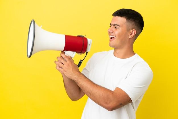Junger gutaussehender mann über isoliertem gelbem hintergrund, der durch ein megaphon schreit, um etwas anzukündigen