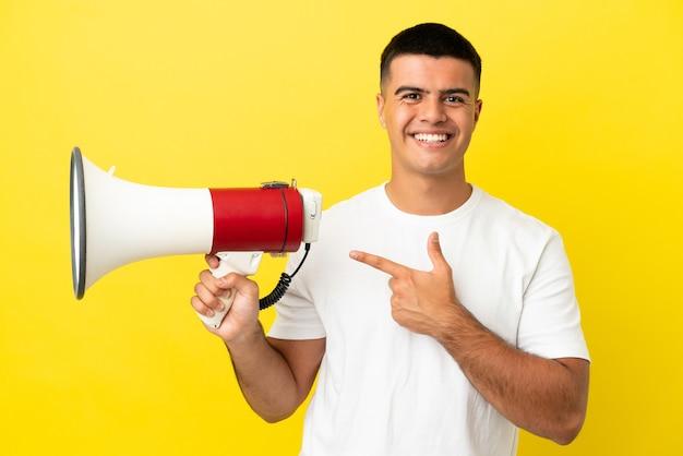 Junger gutaussehender mann über isoliertem gelbem hintergrund, der ein megaphon hält und auf die seite zeigt