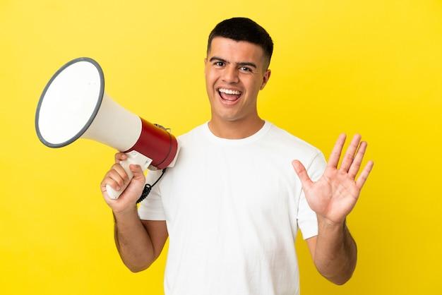 Junger gutaussehender mann über isoliertem gelbem hintergrund, der ein megaphon hält und mit der hand mit glücklichem ausdruck grüßt