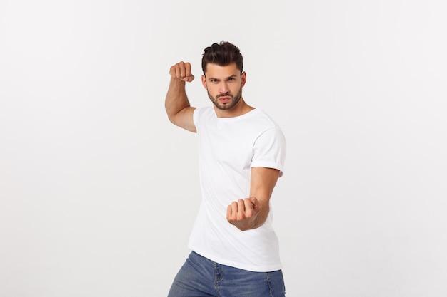 Junger gutaussehender mann über isolierter mauer faust schlagen, um zu kämpfen, aggressiver und wütender angriff, bedrohung und gewalt