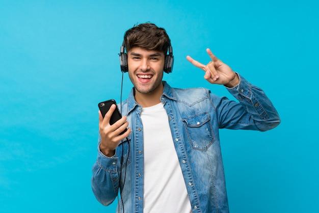 Junger gutaussehender mann über lokalisiertem blau unter verwendung des mobiles mit kopfhörern und dem gesang
