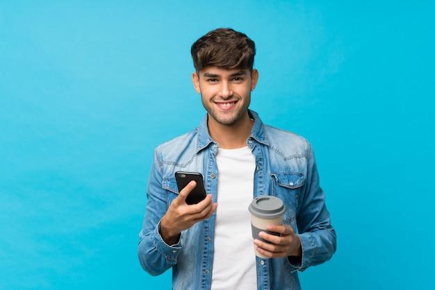 Junger gutaussehender mann über lokalisiertem blauem haltenem kaffee zum mitnehmen und einem mobile