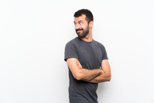 Junger gutaussehender mann über lokalisiertem weiß mit den armen gekreuzt und glücklich