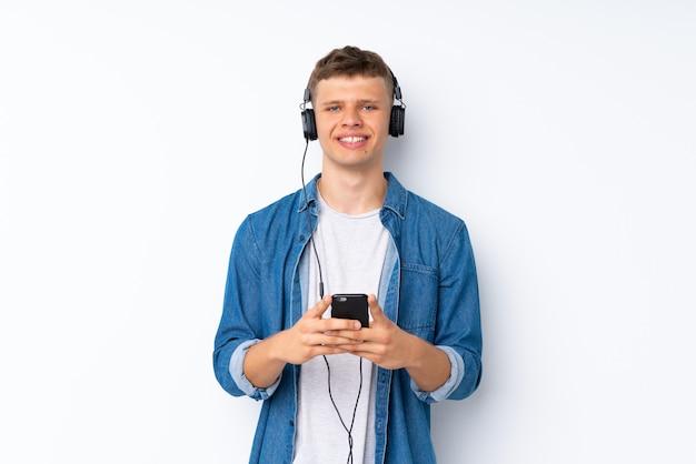Junger gutaussehender mann über lokalisiertem weißem hintergrund unter verwendung des mobiles mit kopfhörern