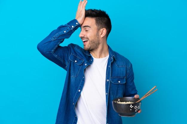 Junger gutaussehender mann über lokalisierter blauer wand hat etwas verwirklicht und die lösung beim halten einer schüssel nudeln mit essstäbchen beabsichtigt