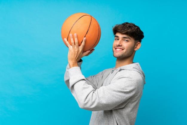 Junger gutaussehender mann über lokalisierter blauer wand mit ball des basketballs