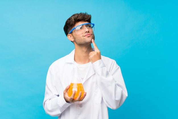 Junger gutaussehender mann über lokalisierter blauer wand mit einem wissenschaftlichen reagenzglas