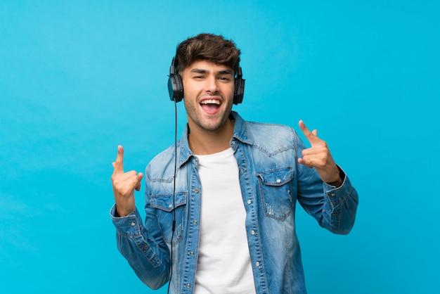 Junger gutaussehender mann über lokalisierter blauer wand unter verwendung des mobiles mit kopfhörern und tanzen