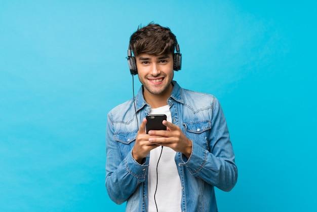 Junger gutaussehender mann über lokalisierter blauer wand unter verwendung des mobiles mit kopfhörern