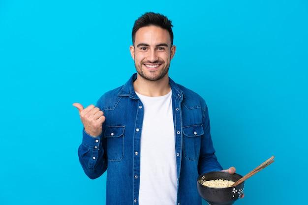 Junger gutaussehender mann über lokalisierter blauer wand zeigend auf die seite, um ein produkt beim halten einer schüssel nudeln mit essstäbchen darzustellen