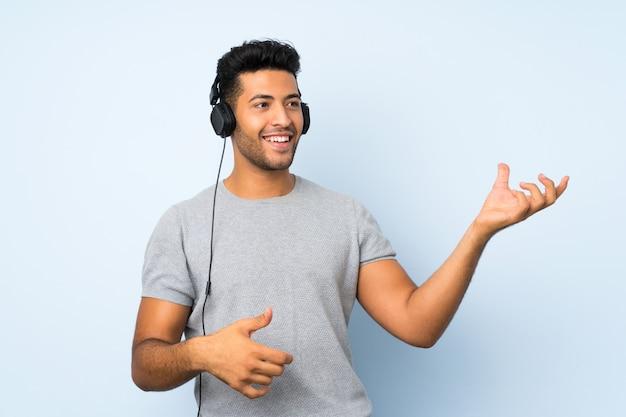 Junger gutaussehender mann über lokalisierter wand unter verwendung des mobiles mit kopfhörern und tanzen