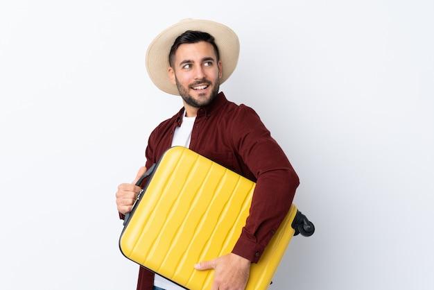 Junger gutaussehender mann über lokalisierter weißer wand in den ferien mit reisekoffer und einem hut