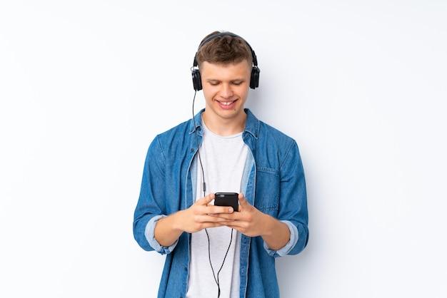 Junger gutaussehender mann über weiß unter verwendung des mobiles mit kopfhörern