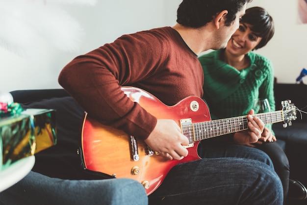 Junger gutaussehender mann und frau, die gitarre spielen