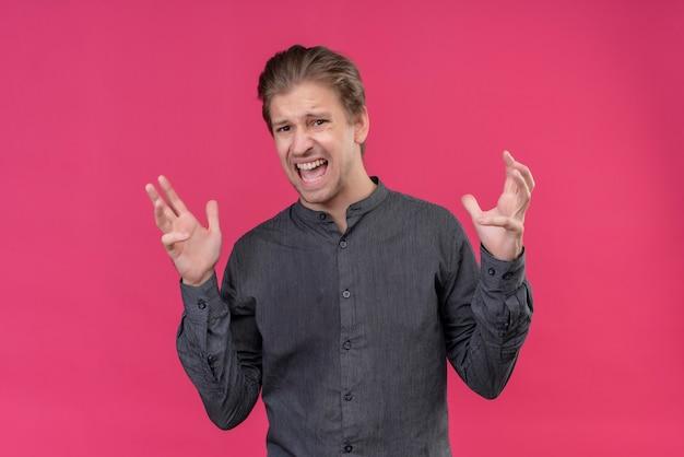 Junger gutaussehender mann verrückt und verrückt, die mit aggressivem ausdruck schreien und schreien
