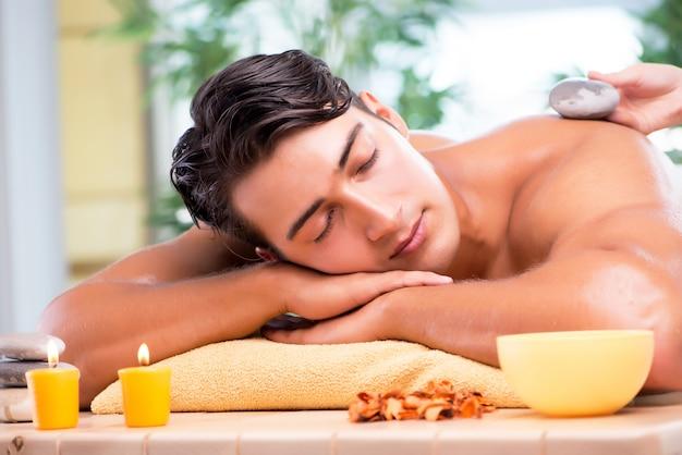 Junger gutaussehender mann während des badekurortverfahrens