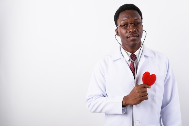 Junger gutaussehender mannarzt, der brillen gegen weiß trägt
