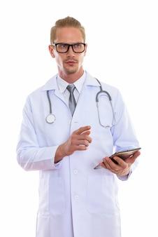 Junger gutaussehender mannarzt, der digitales tablett beim denken hält