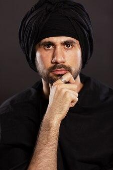 Junger gutaussehender mannmann im moslemischen turban. schwarzer hintergrund