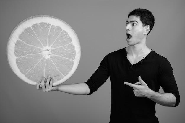 Junger gutaussehender persischer mann gegen graue wand in schwarz und weiß