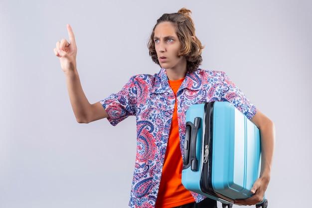 Junger gutaussehender reisender kerl, der koffer gestikulierend hält, warten eine minute mit ernstem selbstbewusstem ausdruck auf gesicht stehend