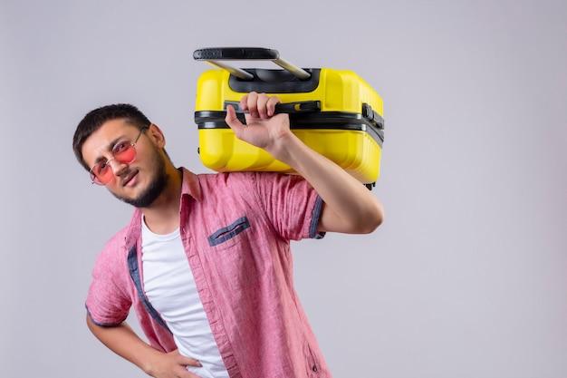 Junger gutaussehender reisender kerl, der sonnenbrille hält, die koffer auf schulter hält, die müde leidet und unter schwerem gewicht steht, das über weißem hintergrund steht