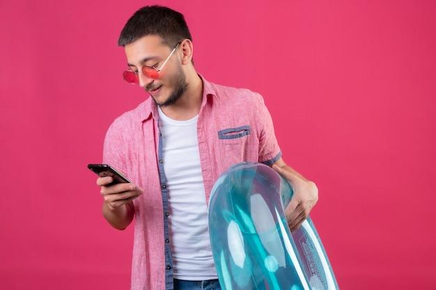 Junger gutaussehender reisender kerl, der sonnenbrillen hält, die aufblasbaren ring halten, der bildschirm seines mobilen lächelnden selbstbewussten stehens über rosa hintergrund betrachtet