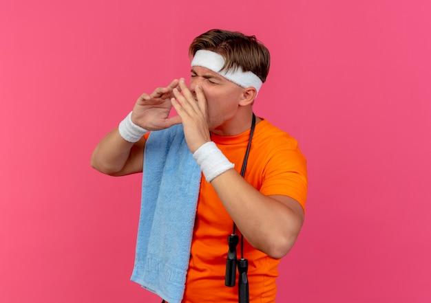 Junger gutaussehender sportlicher mann mit stirnband und armbändern mit handtuch und springseil um den hals, der die hände um den mund legt und laut zu jemandem mit geschlossenen augen schreit