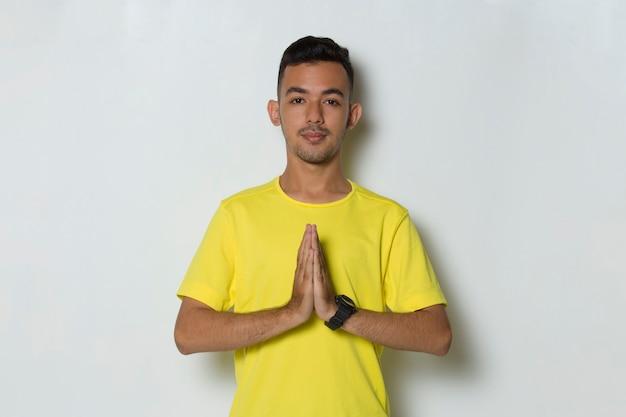 Junger gutaussehender sportmann, der yoga tut, entspannendes meditieren auf weißem hintergrund
