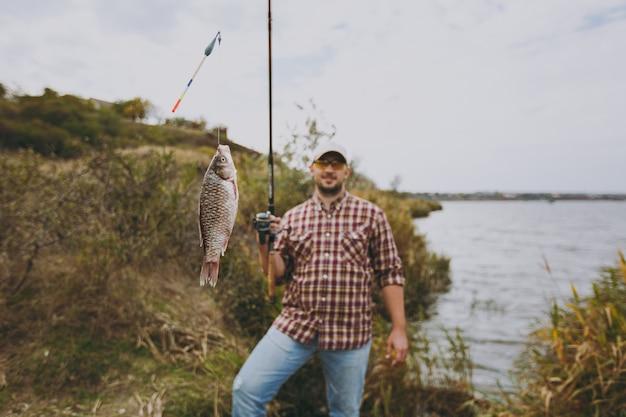 Junger gutaussehender unrasierter mann in kariertem hemd, mütze und sonnenbrille hält eine angelrute mit gefangenem fisch am ufer des sees in der nähe von sträuchern und schilf. lifestyle, erholung, freizeitkonzept für fischer