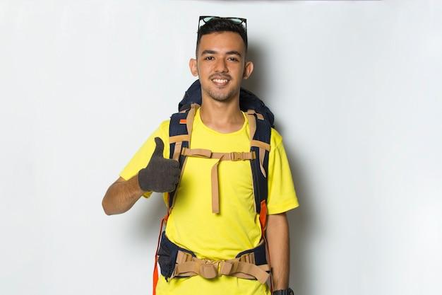 Junger gutaussehender wanderer mit rucksack, der einen daumen hoch zeigt, ok geste auf weißem hintergrund