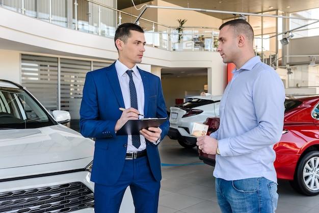 Junger händler, der neues auto an männlichen kunden verkauft und dokumente ausfüllt