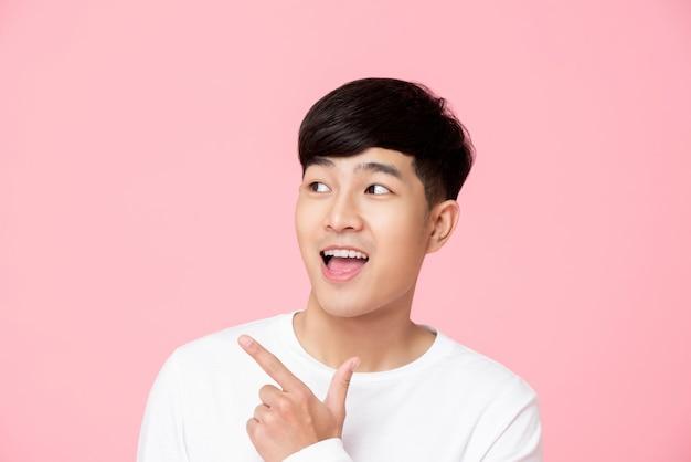 Junger handnsome asiatischer mann, der hand auf leeren raum zeigt