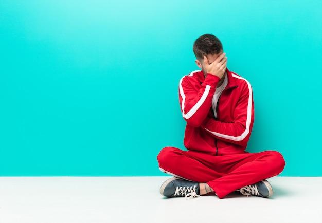 Junger handosme mann, der betont, beschämt oder, mit kopfschmerzen gestört schaut und gesicht mit der hand gegen flache farbwand bedeckt