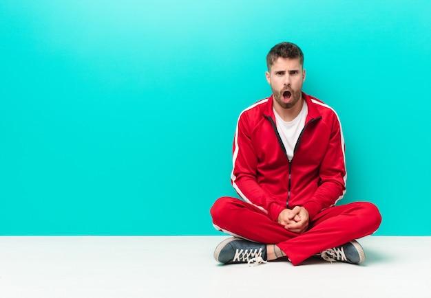 Junger handosme mann, der entsetzt, verärgert, gestört oder enttäuscht, mit offenem mund und wütend gegen flache farbwand schaut
