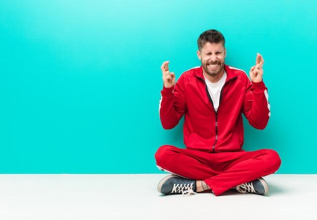 Junger handosme mann, der nervös und hoffnungsvoll sich fühlt, finger kreuzt, für gutes glück gegen flache farbwand betet und hofft
