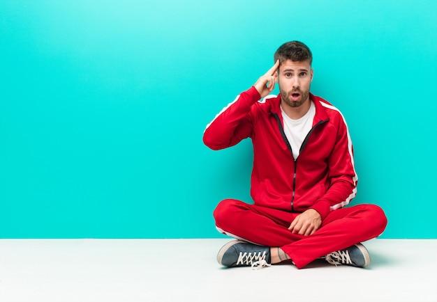 Junger handosme mann, der überrascht, mit offenem mund, entsetzt schaut und einen neuen gedanken, eine idee oder ein konzept gegen flache farbwand verwirklicht