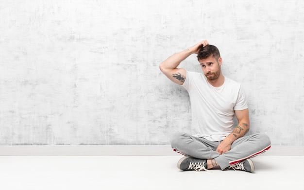 Junger handosme mann, der verwirrt und verwirrt sich fühlt, kopf verkratzt und zur seite gegen flache farbwand schaut