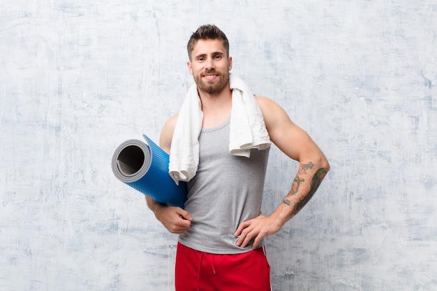 Junger handosme mann gegen wand mit yogamatte. sport-konzept