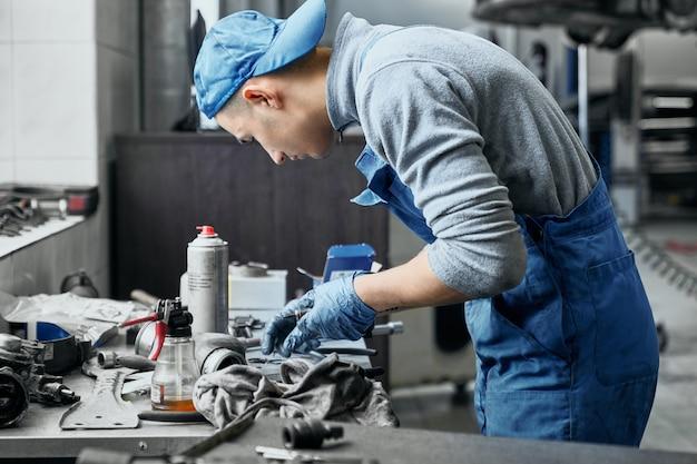 Junger handwerker, der alte details für auto wiederherstellt
