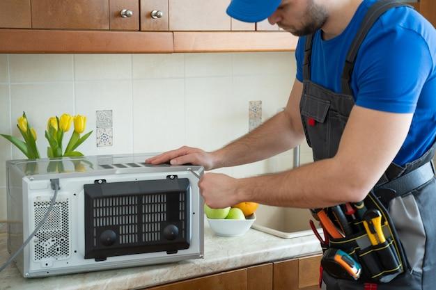 Junger handwerker, der mikrowellenherd durch schraubendreher in der küche repariert und repariert