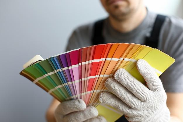 Junger handwerker in der besonderen uniform, die helle farbpalette für innendetails über grauem wandhintergrund hält. professioneller handwerker während des arbeitskonzepts