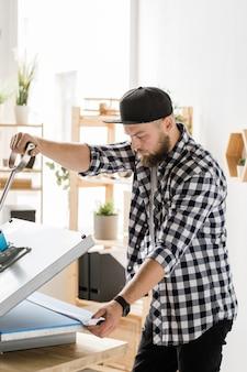 Junger handwerker in der freizeitkleidung, die verzierung auf neuem handgemachtem haustierhalsband druckt, während er neue ausrüstung verwendet