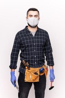 Junger handwerker in freizeitkleidung, schutzmaske und handschuhen, die diy-handwerkzeuge halten, während möbel oder haus repariert werden