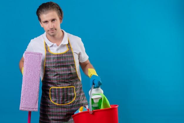 Junger hansdome-mann, der schürze und gummihandschuhe hält, die eimer mit reinigungswerkzeugen halten