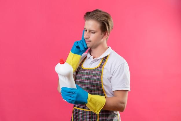 Junger hansdome mann, der schürze und gummihandschuhe hält, die flasche mit reinigungsmitteln halten, die es mit nachdenklichem ausdruck betrachten denkend stehen über rosa wand betrachten