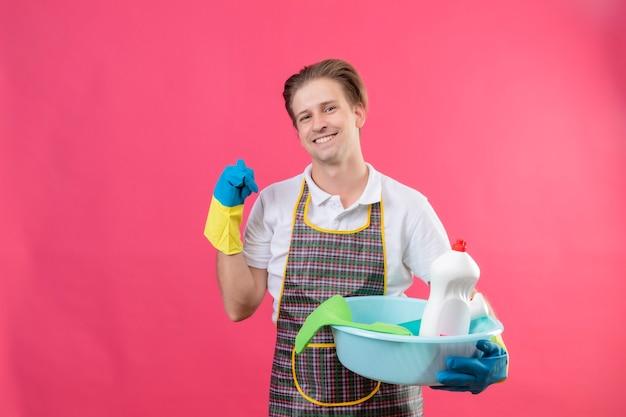 Junger hansdome-mann, der schürze und gummihandschuhe trägt, die becken mit den reinigungswerkzeugen halten, die lächelnd auf etwas hinten mit dem daumen lächelnd stehen über rosa wand zeigen