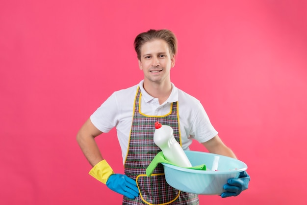 Junger hansdome-mann, der schürze und gummihandschuhe trägt, die becken mit reinigungswerkzeugen mit dem selbstbewussten lächeln auf gesicht halten, das über rosa wand steht