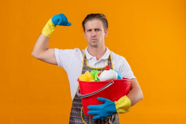 Junger hansdome-mann, der schürze und gummihandschuhe trägt, die eimer mit reinigungswerkzeugen halten, die faust mit ernstem gesicht heben